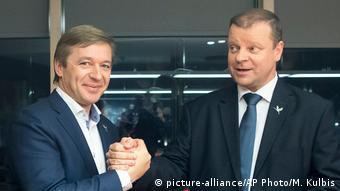 Глава крестьян Рамунас Карбаускис (слева) и лидер партийного списка Саулюс Сквернялис пожимают друг друг руки