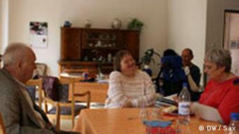 Elderly and infirm people sit in a common room around a table chatting.