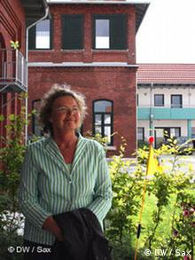 Susanne Tatje sits in front of a plant with a large brick building in the background.
