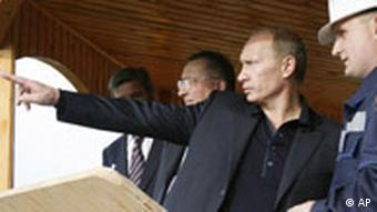 Prime Minister Vladimir Putin, center, gestures as he visits the oil port of Kozmino