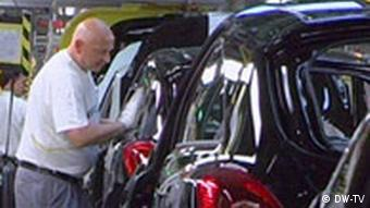 Opel workers inspect cars on assembly line