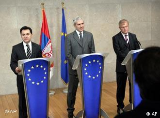 Serbia's Deputy Prime Minister Bozidar Djelic, left, along with Serbia's President Boris Tadic, center, and European Union Commissioner for Enlargement Olli Rehn, right at podium with EU flag of yellow stars against royal blue background
