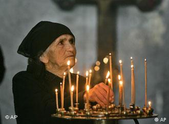 Женщина ставит зажженую свечу перед иконой в православном храме