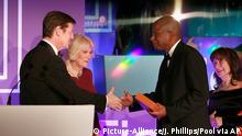 Luke Ellis and Camilla, Duchess of Cornwall present shortlisted author Paul Beatty with a copy of his book 'The Sellout ' at the 2016 Man Booker Prize at The Guildhall in London Tuesday Oct. 25, 2016. Paul Beatty's The Sellout, a stinging satire of race and class in the United States, has won the prestigious Man Booker Prize. (John Phillips / Pool via AP)