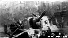 ARCHIV - Drei ungarische Kämpfer gehen am 30.10.1956 vor einem zerstörten russischen Panzer entlang in der ungarischen Hauptstadt Bundapest. Am 23. Oktober 1956 brach in Ungarn ein bewaffneter Aufstand aus, der den Traum von Unabhängigkeit und einem Sozalismus mit einem menschlichen Antliz für wenige Tage greifbar erscheinen ließ. Der Aufstand wurde am 4. November 1956 von sowjetischen Truppen niedergeschlagen. Foto: dpa (nur s/w - zu dpa «Neun Monate im Todestrakt - Wie Imre Mecs den Ungarn-Aufstand erlebte» vom 21.10.2106) +++(c) dpa - Bildfunk+++