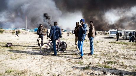 A group of young migrant boys stand near the Jungle in Calais. Camp residents lit several fires as police cleared the area on October 26.