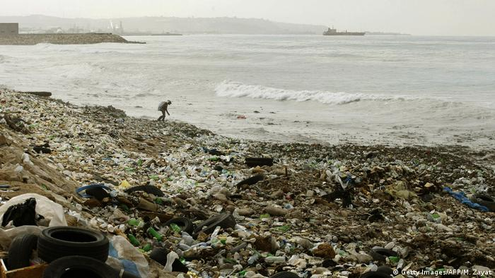 A Lebanese collects recyclable waste as he walks along a garbage dump spilling into the Mediterranean sea in the southern Lebanese city of Sidon