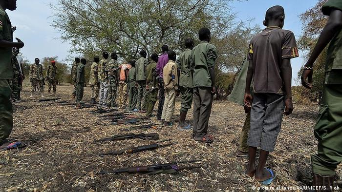 South Sudanese child soldiers standing with their weapons on the floor