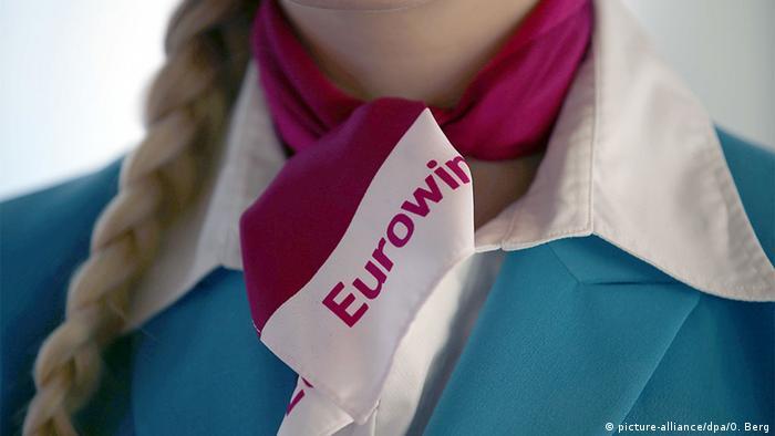 Стюардесса Eurowings в униформе и шейном платке с логотипом компании.