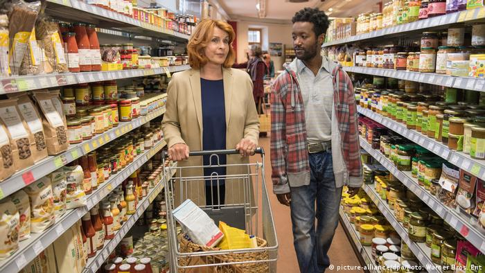 A German woman and a Nigerian refugee walk down a grocery store aisle in a scene from the 2016 movie Welcome to Germany (picture-alliance/dpa/Foto: Warner Bros. Ent)