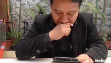 Cesar Canil reads on his smartphones