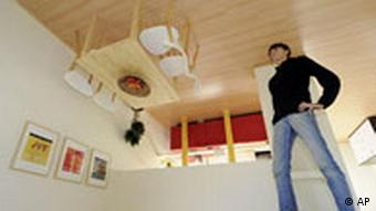 Woman standing in room with furniture on ceiling