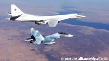SYRIA. NOVEMBER 21, 2015. A Sukhoi SU-30SM fighter aircraft escorts a Tupolev Tu-160 strategic bomber of the Russian Air Force's long-range aviation during airstrikes against ISIS targets in Syria. Video screen grab. Russian Defence Ministry's Press and Information Department/TASS |