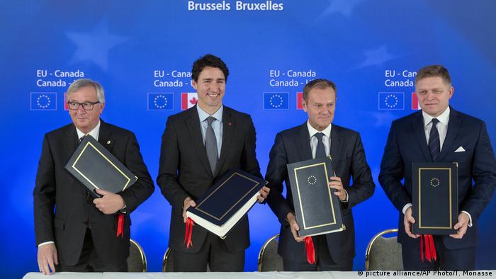 Canadian Prime Minister Justin Trudeau, second left, stands with, from left, European Commission President Jean-Claude Juncker, European Council President Donald Tusk and Slovakian Prime Minister Robert Fico after signing the Comprehensive Economic and Trade Agreement (CETA) during an EU-Canada summit at the European Council building in Brussels,