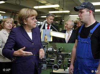 Angela Merkel talking to a trainee on a visit to Berlin