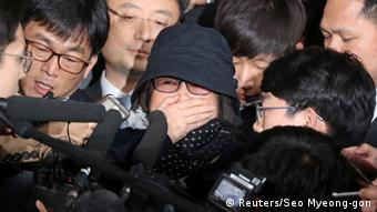 Choi Soon-sil (C) surrounded by the media on her arrival at a prosecutor's office in Seoul, October 31