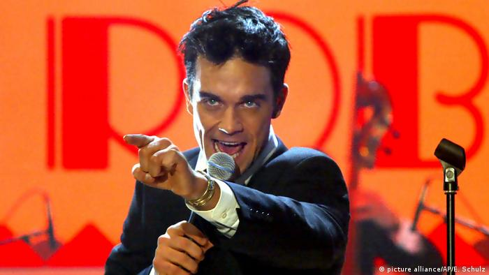 Robbie Williams singing and pointing his finger (Photo: picture alliance/AP/E. Schulz)