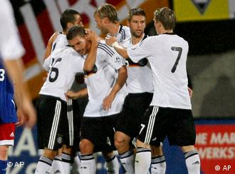 Germany's Lukas Podolski, 2nd from left, is hugged by teammates after he scored the opening goal against Liechtenstein during their World Cup group 4 qualifying soccer match in Vaduz, Liechtenstein, Saturday, Sept. 6, 2008.