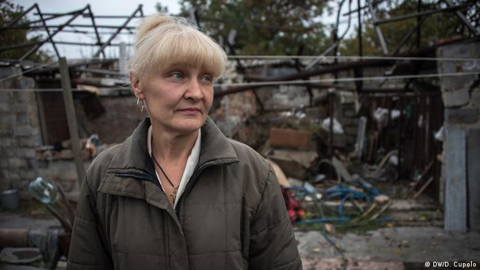 Світлана Заваденко стоїть перед своїм зруйнованим будинком у Спартаку