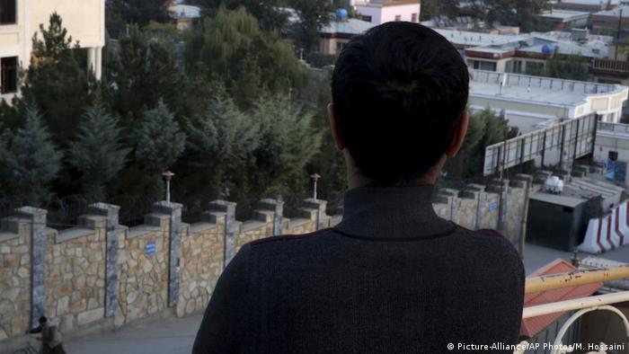 A young gay Afghan poses with his back to the camera in Kabul