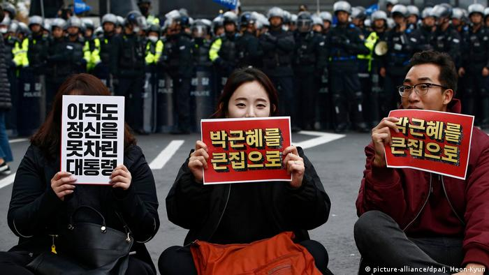 South Koreans sit in front of the police with a banner reading Park Geun-hye Out during a protests against the president in the capital Seoul