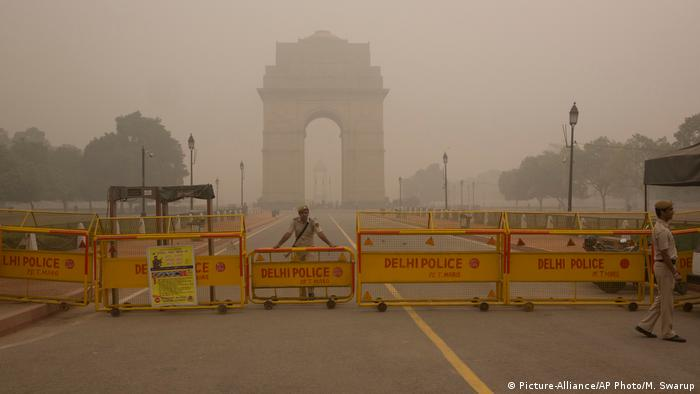 A Delhi policeman stands guard at the war memorial India Gate engulfed in a thick smog in New Delhi