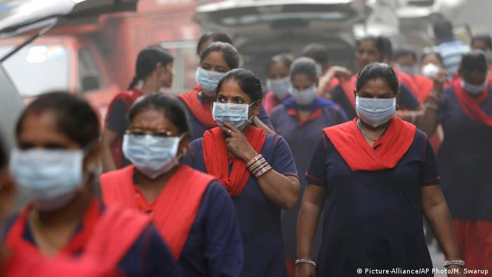 A group of Indian women wear pollution masks arrive to a protest against air pollution in New Delhi, India