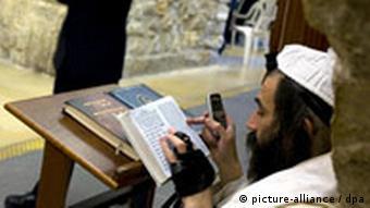 یک دیندار یهودی با تلفن همراه در کنار دیوار ندبه