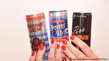 Zwei Hände mit lackierten Fingernägeln halten mehrere Energy-Drinks (picture-alliance/dpa/R. Fellens)