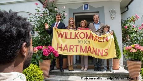 Film still of Willkommen bei den Hartmanns with a family carrying a welcome poster (picture-alliance/dpa/Warner Bros. Ent.)