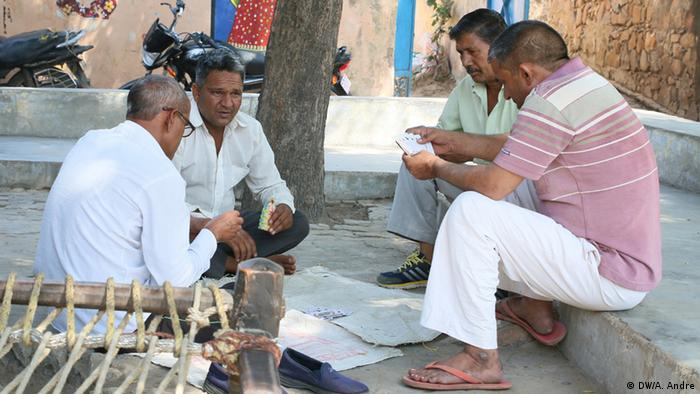 Four men sit together in a village square (DW/A. Andre)