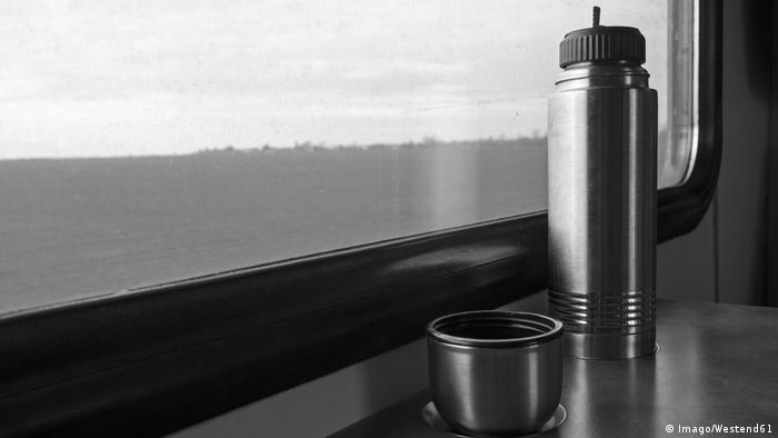 Eine Thermoskanne steht auf einem Fensterbrett in einem Zug (Foto: Imago/Westend61)