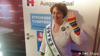 A Clinton supporter wears a sash reading 'Votes for Women'