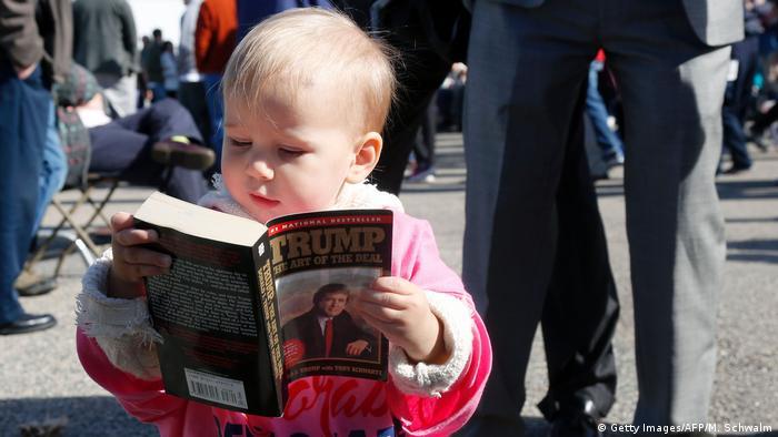 Ребенок листает книгу - биографию Дональда Трампа