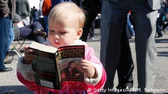 Ένας μπόμπιρας στις ΗΠΑ φυλλομετρά βιβλίο του Τραμπ