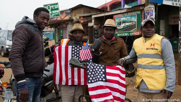 Several men standing in front of shacks, holding American flags