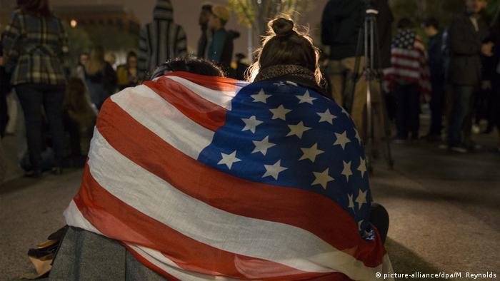 Сторонницы Хиллари Клинтон плачут, завернувшись в национальный флаг США, после оглашения итогов голосования