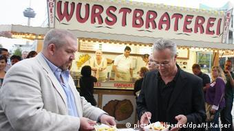Pommesbude in Köln, im Vordergrund essen zwei grauhaarige Männer Pommes mit Ketschup und Mayo an einem Stehtisch.