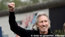 British musician Roger Waters clenches his fist as he addresses the crowd in front of remains of the Berlin wall (East side gallery) on the eve of his show, The Wall at the Olympic stadium in Berlin on September 3, 2013. Waters lent his support to the movement that wants to preserve the 1,3km long stretch of the cold war symbol and keep the land along the river Spree as public land. AFP PHOTO / ODD ANDERSEN (Photo credit should read ODD ANDERSEN/AFP/Getty Images)