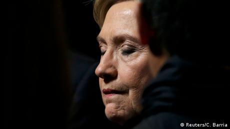 Hillary Clintons Gesicht wird angestrahlt, während sie die Augen schließt
