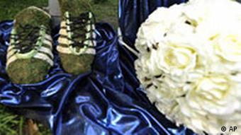 Çimden yapılmış futbol ayakkabısı ve çiçeklerden yapılmış bir top. Bunlar mezar süslemesinde kullanılıyor