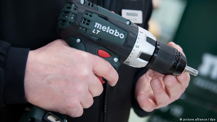 Ein Mann hält eine Bohrmaschine in den Händen (Foto: dpa)