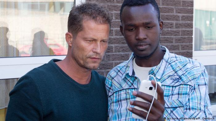 Til Schweiger und ein Flüchtling blicken auf ein Handy (picture-alliance/dpa/F. Gentsch)