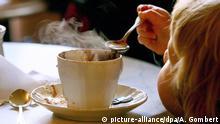 Wärmende Getränke in Deutschland Kind löffelt heißen Kakao