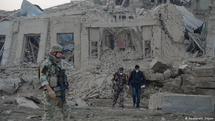 Afghan security forces and NATO troops investigate at the site of explosion