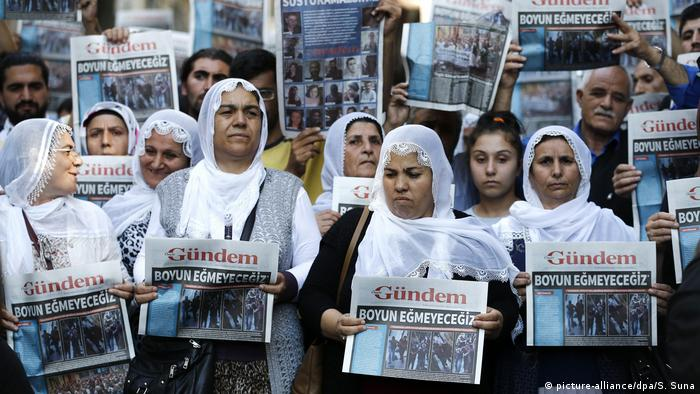 Women hold up newspapers as a form of protest
