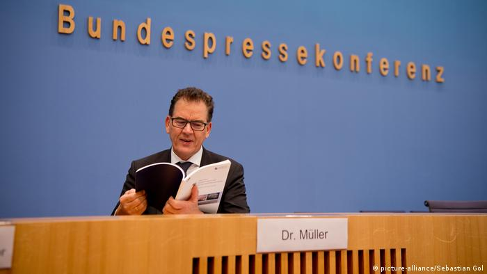 Development minister Gerd Müller reading a copy of the study before the press briefing
