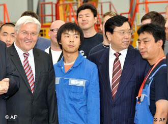 China's Vice Prime Minister Zhang Dejiang, 2nd right, and German Foreign Minister Frank-Walter Steinmeier, left, stand among a group of Chinese trainees in an assembly hall as they visit the Airbus facilities in Hamburg,