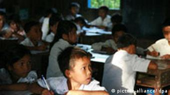 Schoolroom in Cambodia with 6-7 year old students writing in notebooks