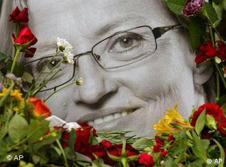 A portrait of late Swedish Foreign Minister Anna Lindh framed with flowers stands in front of a government building in Stockholm, Friday, Sept. 12, 2003. Lindh died Thursday after she was stabbed multiple times in an upscale Stockholm department store by an unknown assailant Wednesday. (AP Photo/Darko Vojinovic)